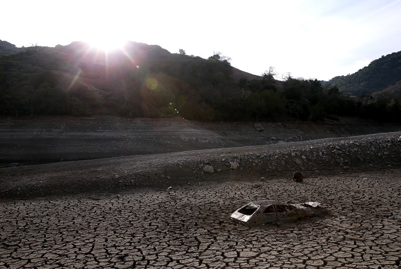 A car sits in dried and cracked earth of what was the bottom of the Almaden Reservoir on January 28, 2014 in San Jose, California.