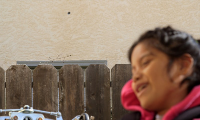 Jacquelyn Funes, 9, on her front porch. A bullet hole can be seen in the wall behind her.