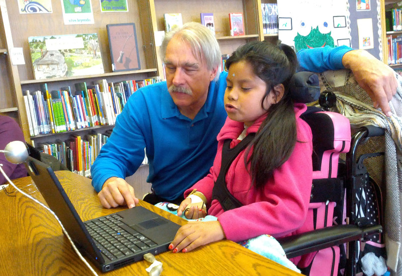 Chris Beatty, assistive technology professional for Oakland's schools, shows Jacquelyn Funes how to operate a laptop with a sensor mounted on her forehead.