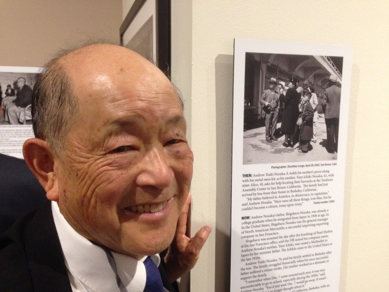 Andrew Nozaka visits the California Museum in Sacramento. He's next to a photo of him and his mother taken by Dorothea Lange at Tanforan in 1942.