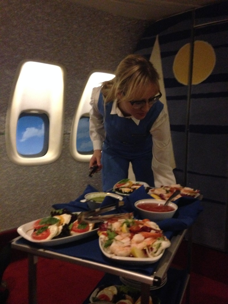 Betsy Holt serves up shrimp salad and other appetizers aboard the Pan Am Experience.
