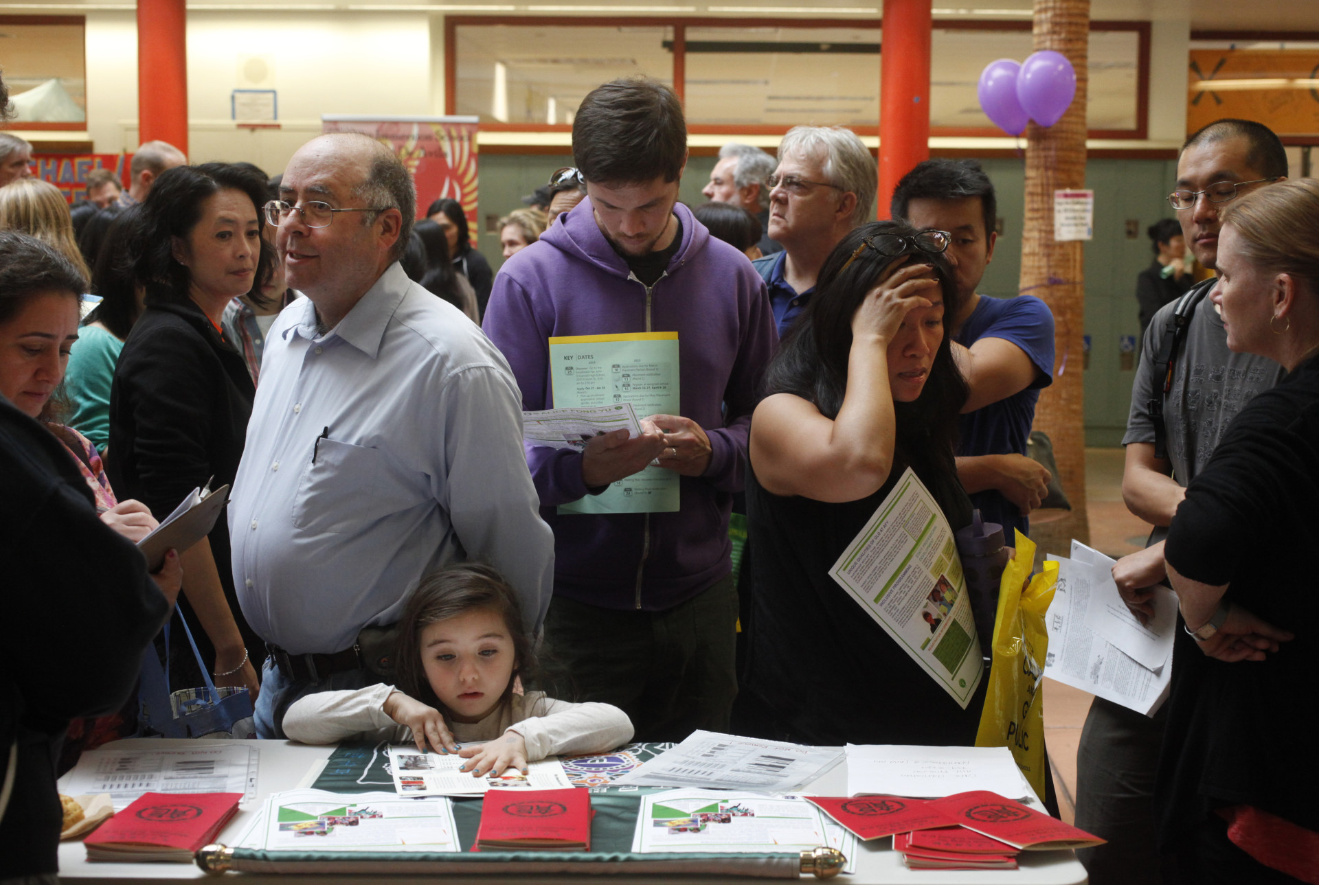 From left, Dina Bakour and Said Nuseiben talk with a representative of Alice Fong Yu Alternative School as Nuseiben's daughter. Kindah Nuseibeh, examines pamphlets while Brendan VanderMei, center, and Lily Tung Crystal, right, chat at the SFUSD school enrollment fair at John O'Connell High School Oct. 25, 2014 in San Francisco, Calif.