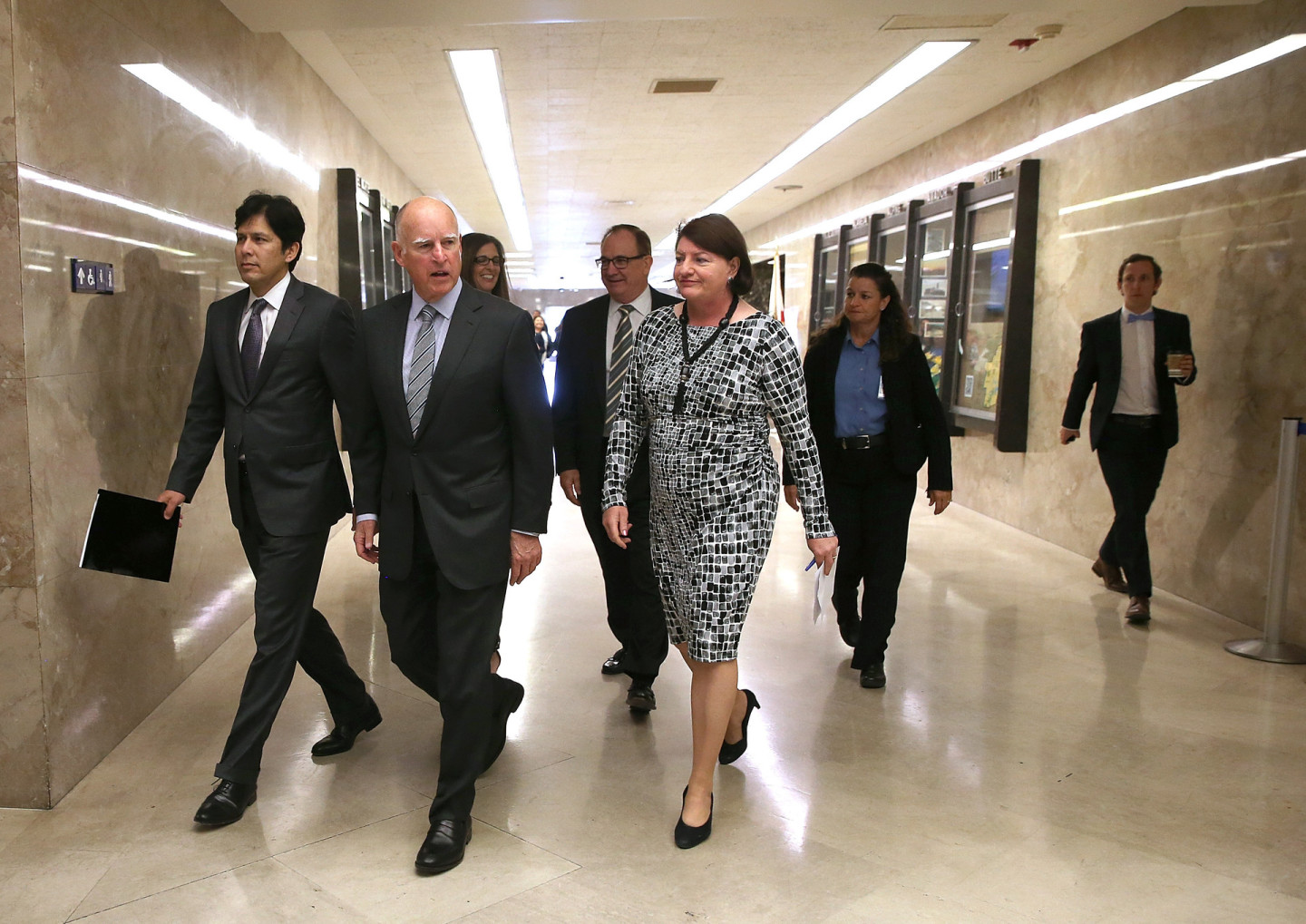 California Gov. Jerry Brown (C) walks with Senate President pro Tempore Kevin de León (L) and Assembly Speaker Toni Atkins (R) to a news conference on March 19, 2015.