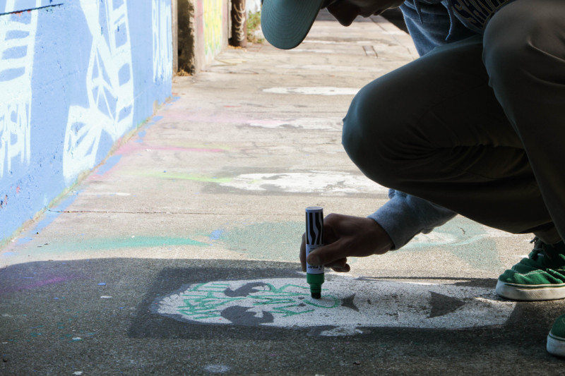 A graffiti writer tags on top of a piece of street art. (Jeremy Raff/KQED)