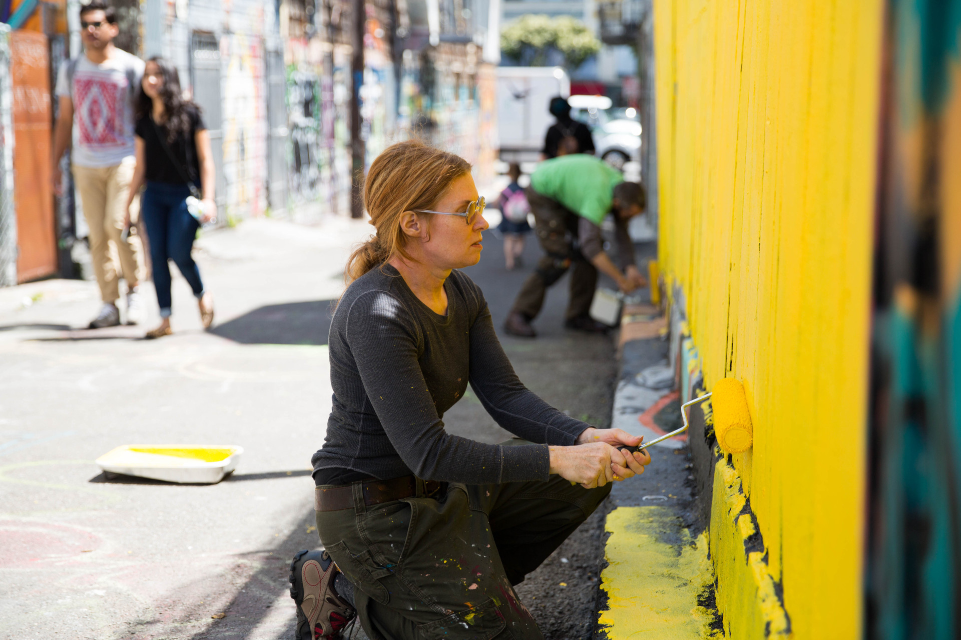 Megan Wilson of the Clarion Alley Mural Project puts up a temporary mural after someone painted a full-scale mural without permission. (Jeremy Raff/KQED)