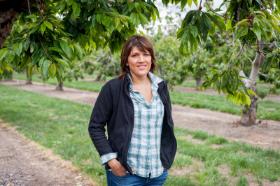 Nicole Rajkovich standing in her family's Bing cherry orchard in Hollister, Calif. (Cynthia E. Wood/KQED)