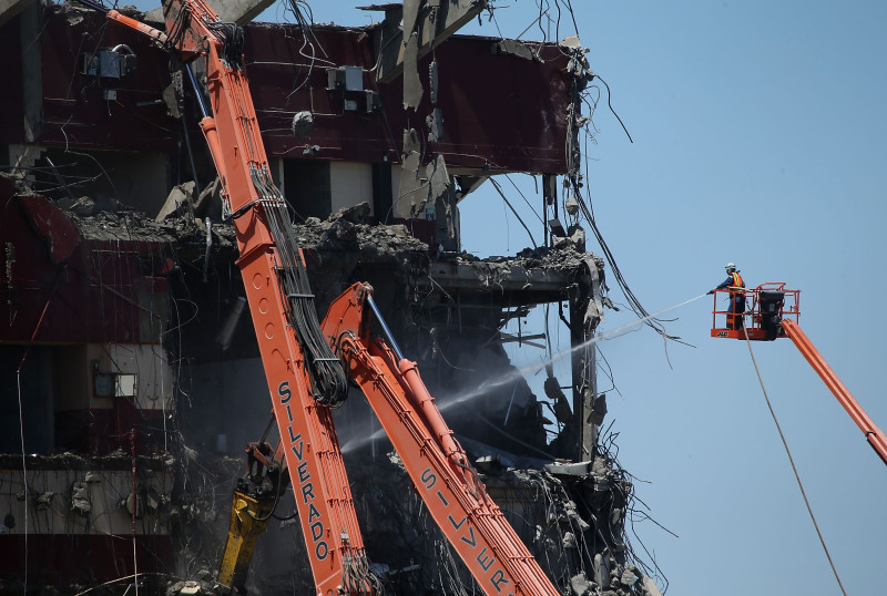 June 9: A worker sprays water on Candlestick rubble.  In January, officials changed their demolition plans after nearby residents complained that the planned implosion would send clouds of potentially toxic dust wafting through the neighborhood.