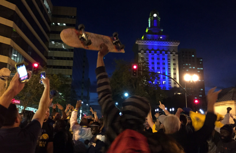 Fans celebrate the Warriors victory in front of Oakland City Hall, which is lit up in Warriors blue and yellow. (Adam Grossberg/KQED)