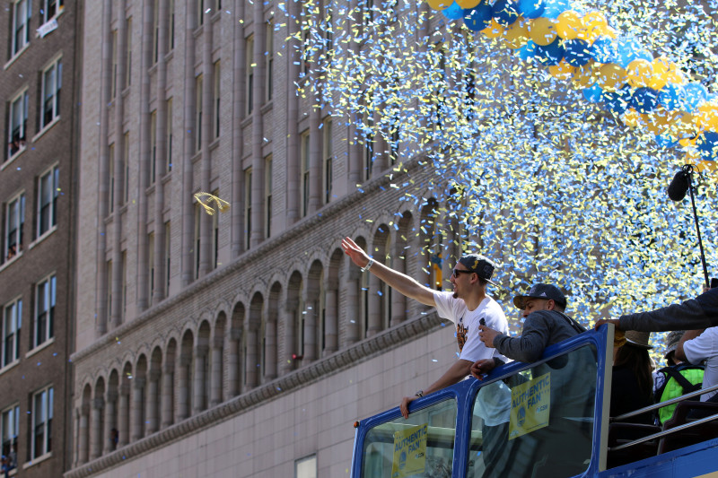 Klay Thompson throw something to the fans during the Warriors Championship parade. (Adam Grossberg/KQED)