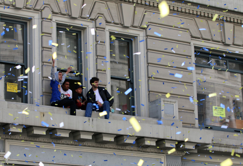 Fans look out at the Warriors parade as it moves down Broadway. (Adam Grossberg/KQED)