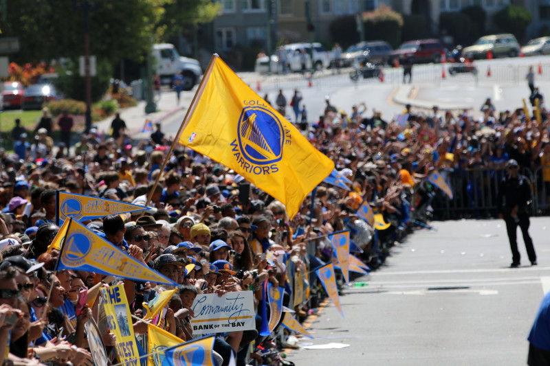 Fans on Grand Avenue cheer as Steph Curry passes by. (Adam Grossberg/KQED).