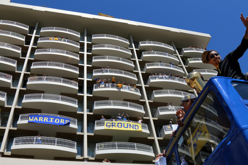 Fans in an apartment building on Lakeside Drive watch Steph Curry and the Warriors celebrate. (Adam Grossberg/KQED)