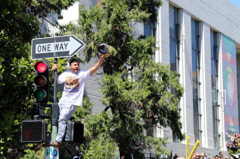 Excited fans packed the streets and climbed on lamp posts and street lights. (Adam Grossberg/KQED)