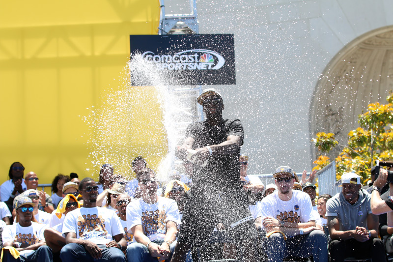 Draymond Green sprays champagne at the Warriors' rally. (Adam Grossberg/KQED)