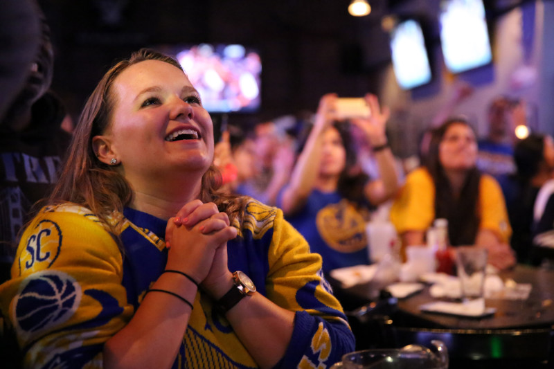 Fans bask in the glory of the Warriors championship at The Grand Oaks Sports Bar in Oakland. (Adam Grossberg/KQED)