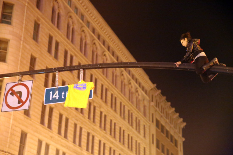 A fan shimmies up a light post at 14th Street and Broadway in Oakland. (Adam Grossberg/KQED)