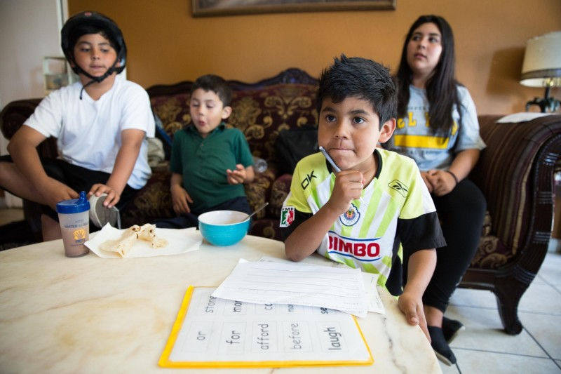Bryan Luque, seven, works on his English homework, with siblings Angel, Valentin and Lidia behind.