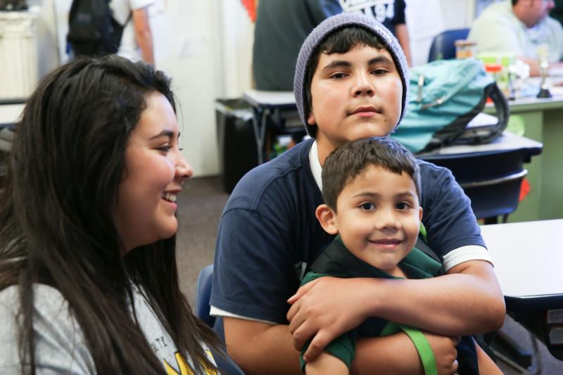 Jose Daniel hugs his little brother Valentin as sister Lidia looks on.