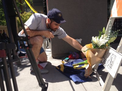 A man leaves flowers at an impromptu memorial for victims of Tuesday's balcony collapse in downtown Berkeley.