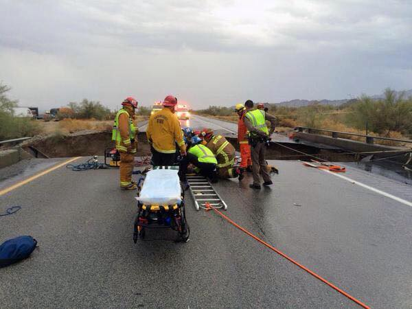 Firefighters and paramedics rescue the driver of a pickup truck that crashed off a collapsed bridge on Interstate 10 near the town of Desert Center.