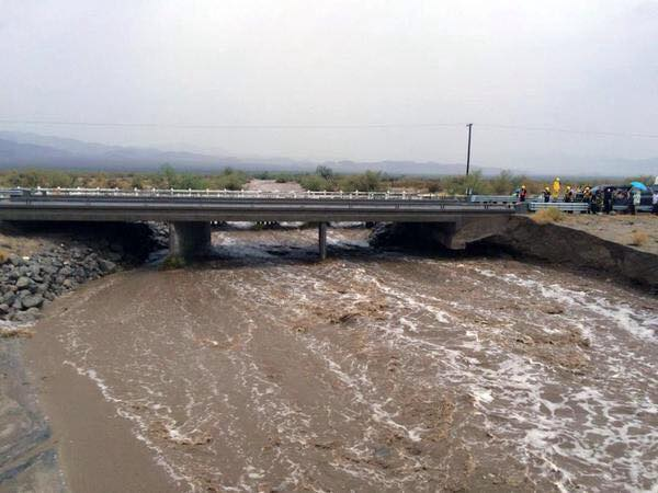 Water surges under the threatened but intact westbound bridge on Interstate 10 near the town of Desert Center on Sunday. The bridge on the eastbound lanes collapsed.