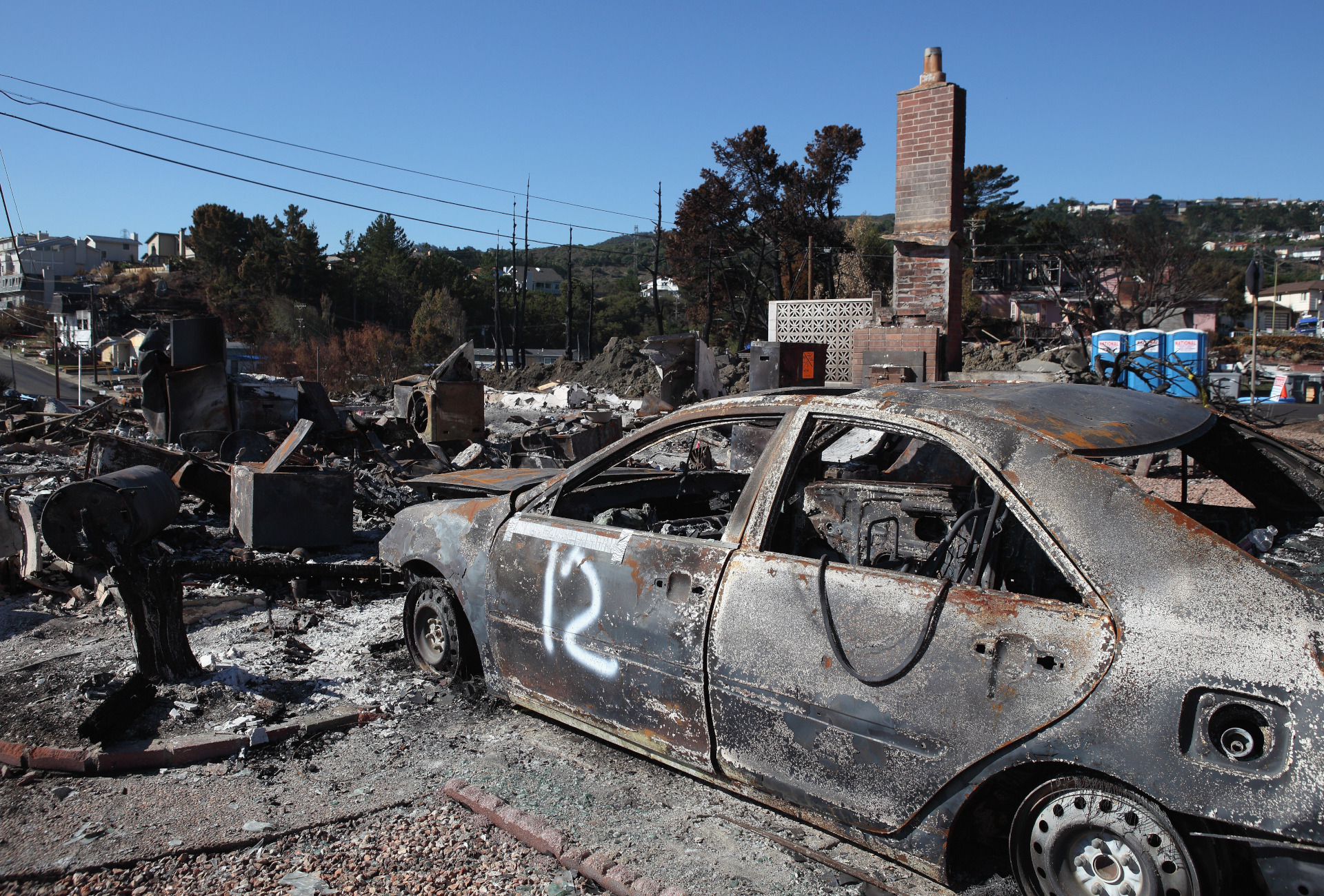The shell of a car sits in the driveway of a burned home near the epicenter of the San Bruno pipeline explosion.