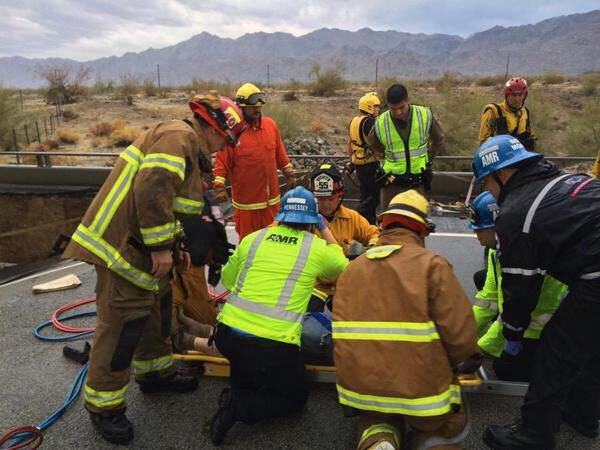 Firefighters and paramedics treat the driver of a pickup truck that crashed off a collapsed bridge on Interstate 10 near the town of Desert Center.