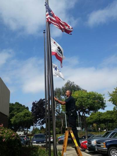 A Hayward police officer lowers a flag at the department to half-staff Wednesday after the fatal shooting of Sgt. Scott Lunger.