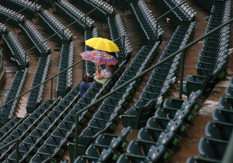 Fans with umbrellas sit in the stands in Anaheim, waiting for the start of the game between the Angels and Boston Red Sox. The game was postponed -- the Angels' first rainout in 20 years.