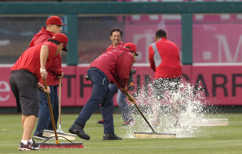 Members of the grounds crew at Angels Stadium in Anaheim tries to clear the outfield of excess water before Sunday's game with the Boston Red Sox. The game was eventually postpone -- the Angels' first rainout since 1995.