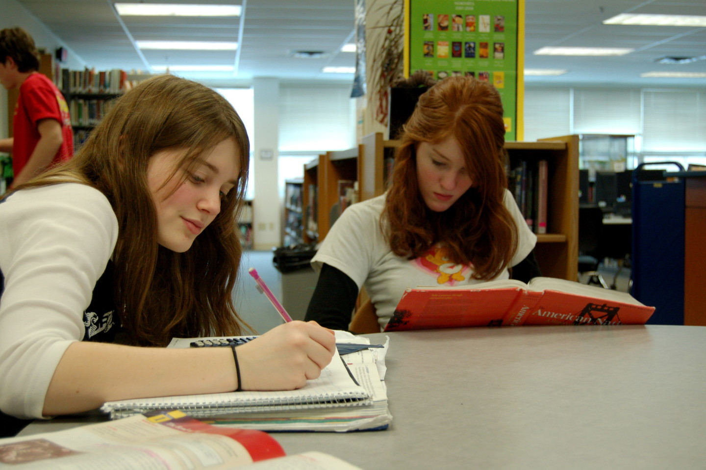Two girls spend time at a library studying math and doing homework.