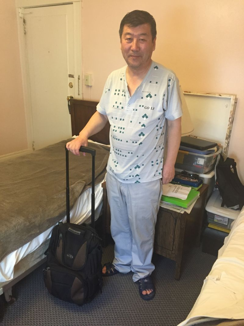 Hotel Astoria resident Paris Wang worries he will be locked out. He never leaves his room without a backpack.