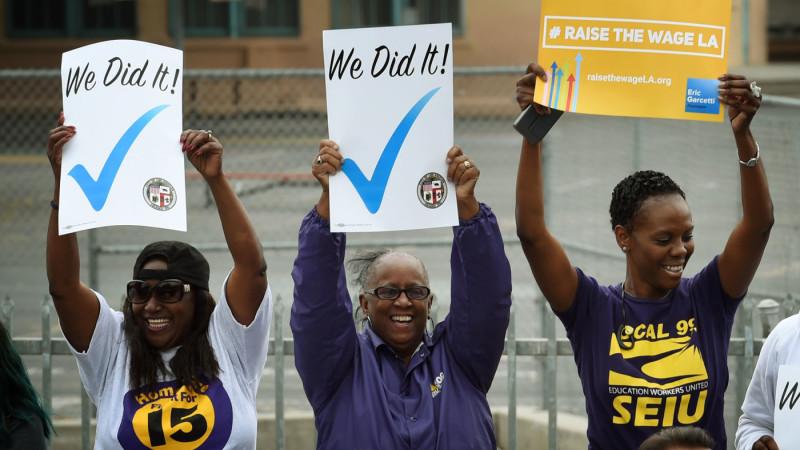 Activistas laborales celebran el 13 de junio del 2015 en lo que el alcalde de Los Ángeles, Eric Garcetti, firma legislación a partir de una ordenanza que eleva el salario mínimo a $15 para el 2020.
