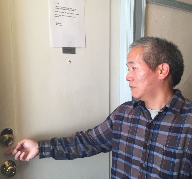 Hotel Astoria resident Owen Wang shows his damaged door. A note above says management has changed the lock.