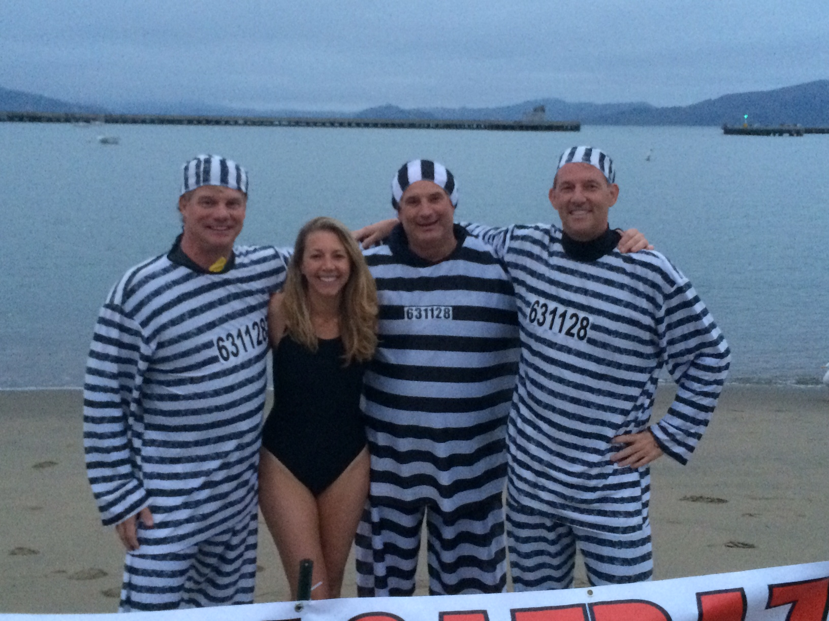 Before the race, three swimmers donned prison garb over their wetsuits and posed for photos near the finish line.