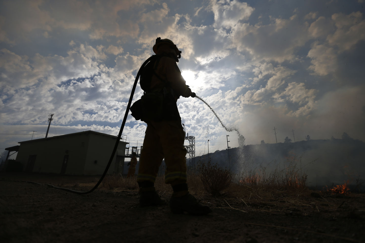 Firefighter douses a backfire set Tuesday  to try to limit the spread of the Jerusalem Fire in Lake County.  Stephen Lam/Getty Images