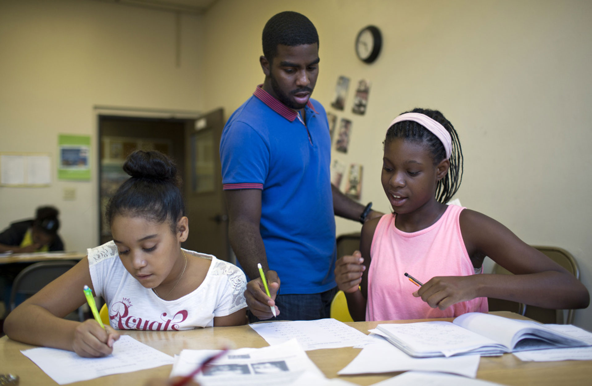 Teaching assistant Jonathan Curtiss checks the work of Alyse Wilson, 11 (L) and Kayla White, 12, during the fourth week of a pre-algebra class at the West Angeles Church Youth Center on Thursday afternoon, July 30, 2015.