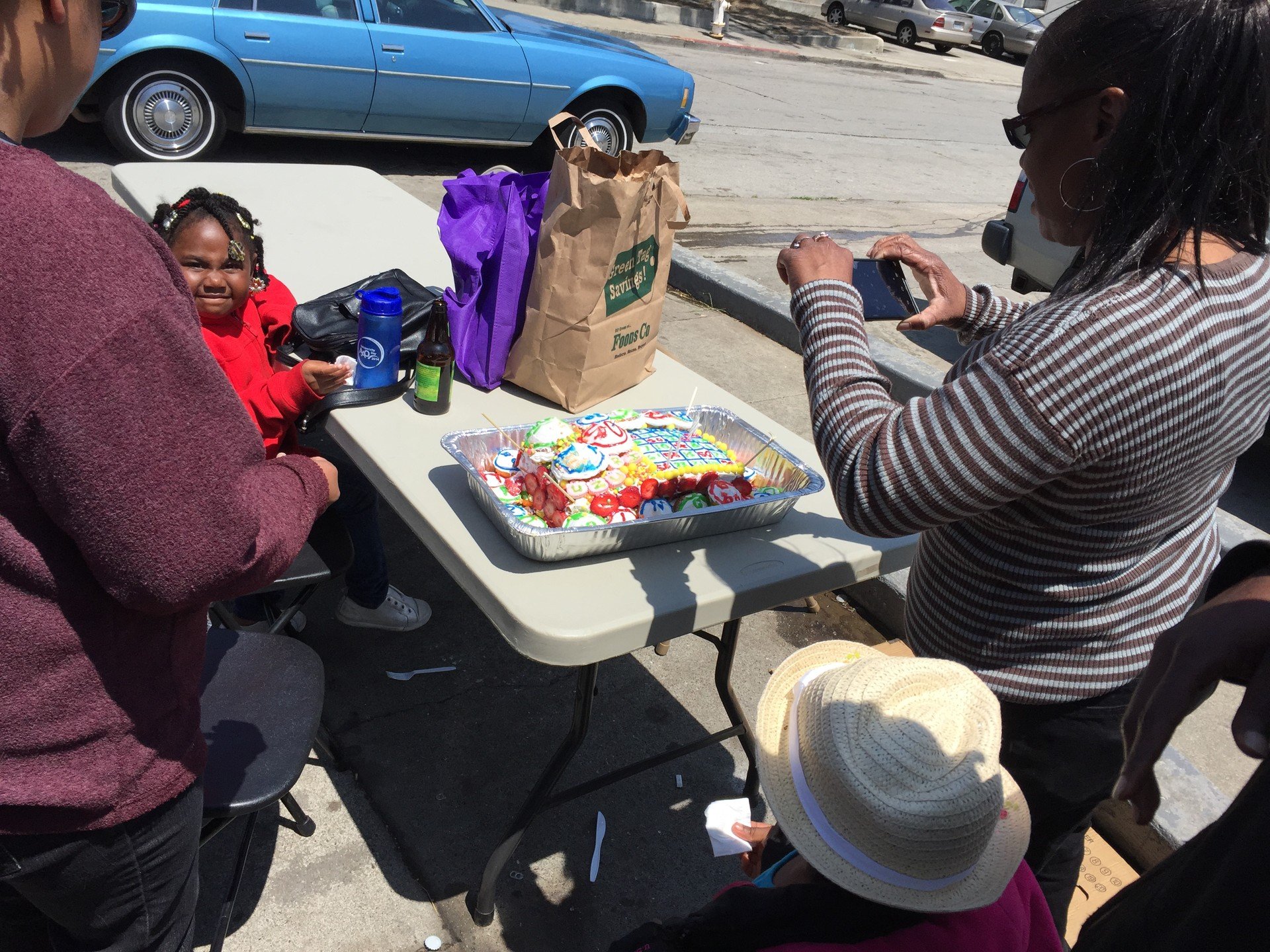 Residents admire a 'Bingo'-themed birthday cake on display at a July 26 barbecue in Potrero Terrace.