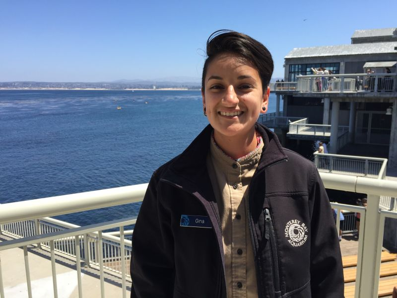 Gina Carrillo stands on a balcony at the Monterey Bay Aquarium overlooking the Monterey Bay.  In high school, Carrillo participated in the Watsonville Area Teens Conserving Habitats  program. Now she works for the Aquarium.