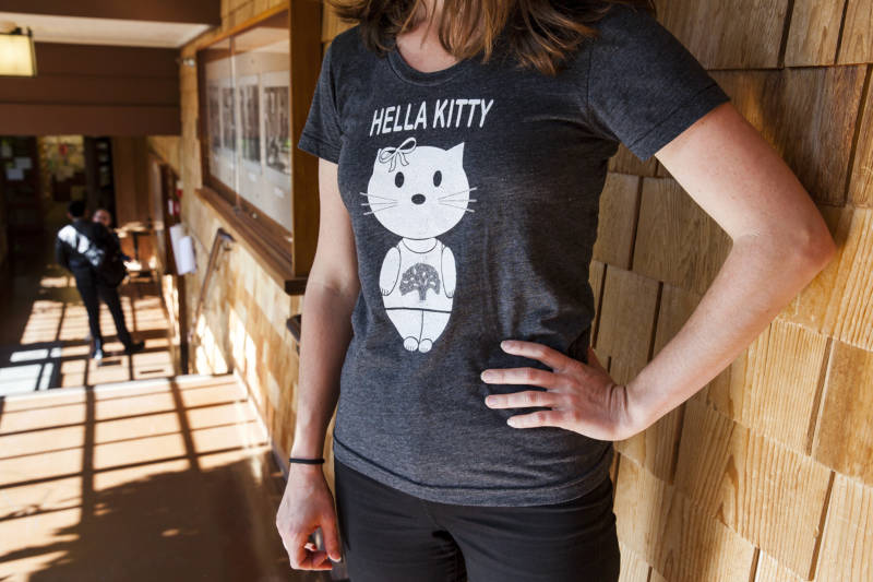 A UC Berkeley student poses for photos wearing a 'Hella Kitty' shirt from Pure 510, a local custom t-shirt business in Oakland, California.