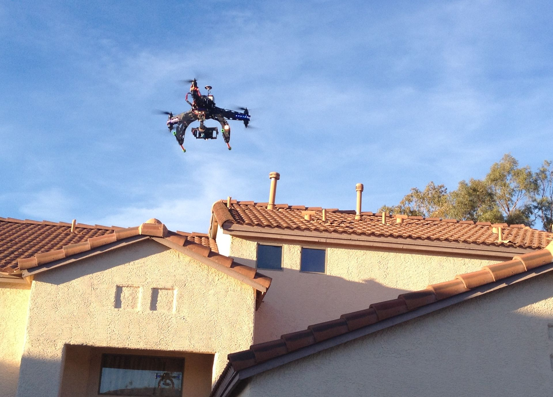 File photo of a unmanned aircraft, or drone, flying over a house.