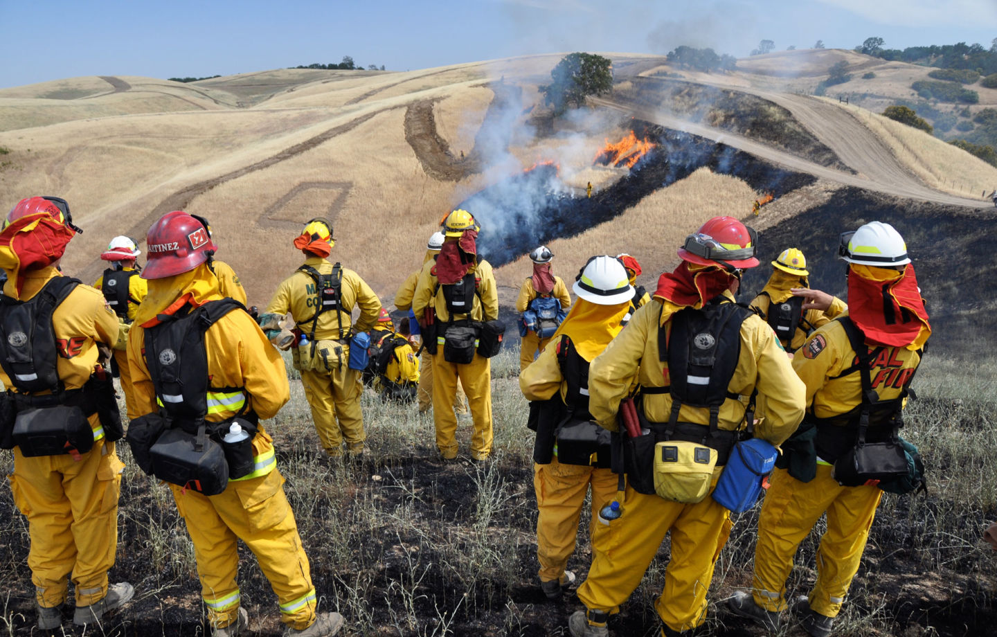 Students and instructors from Cal Fire participate in live fire drills during a week of intensive training designed to teach firefighting operations. Linnea Edmeier/KQED