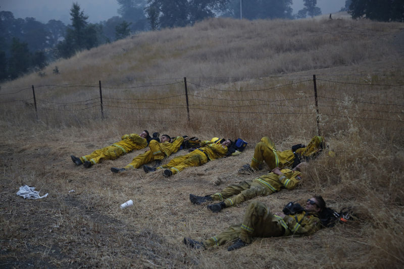 Firefighters with the CalFire Santa Clara Unit rest along Highway 29 during the Valley Fire Middletown, California. (Photo by Stephen Lam/ Getty Images)