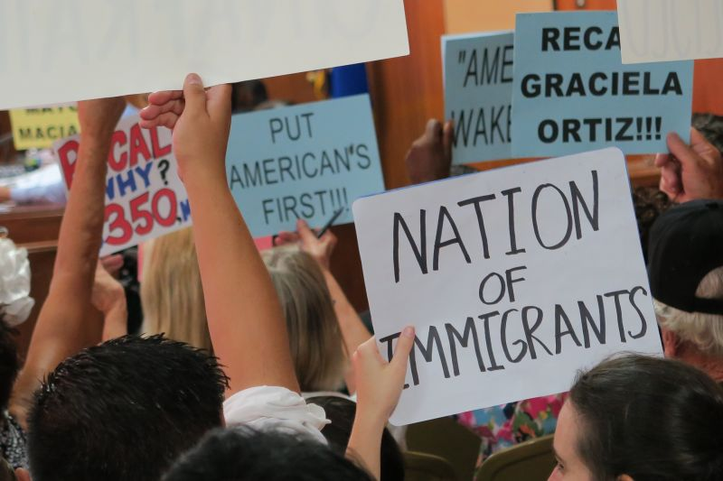 Protest signs hoisted during a recent Huntington Park city council meeting illustrate the divide over the appointment of two undocumented immigrants to city commissions. Organized opposition is supported in large part by activists from outside L.A. County.