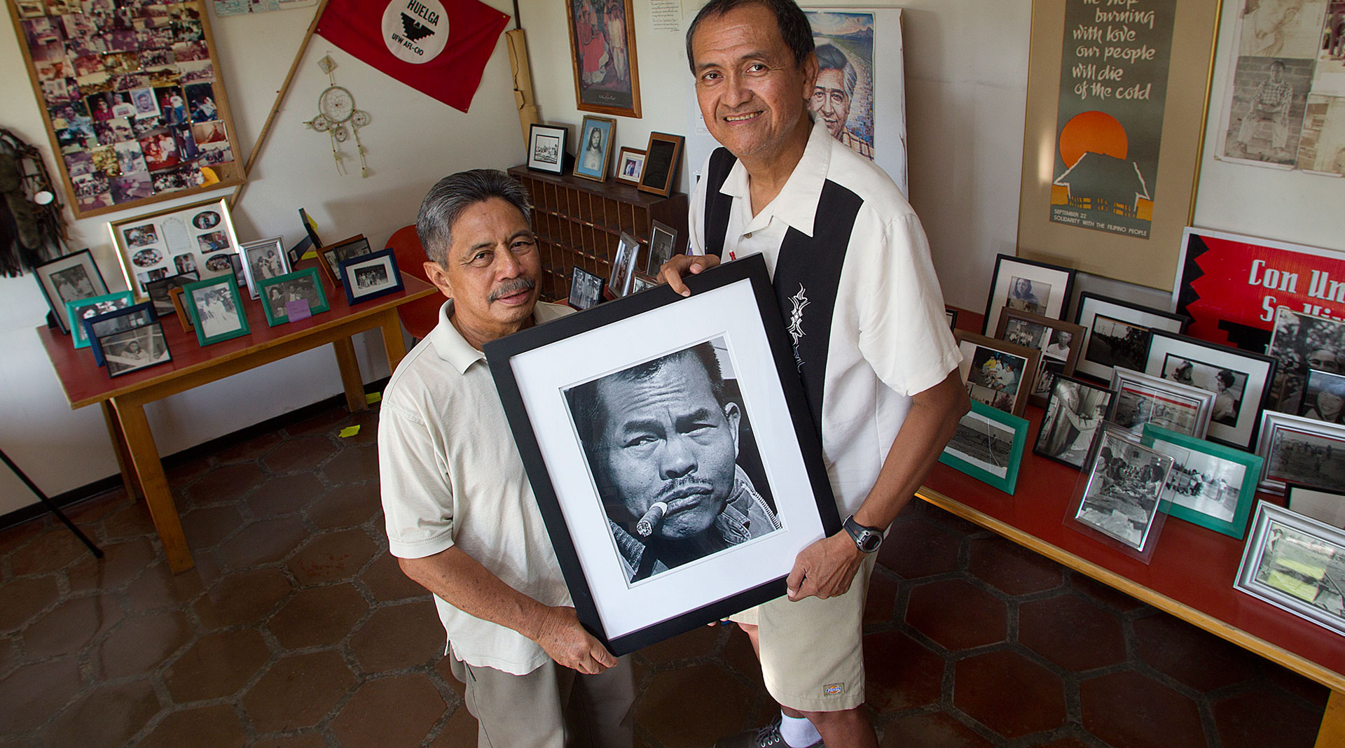 "At the Paulo Agbayani Village west of Delano, Roger Gadiano (L) and Alex Edillor hold a photo of grape strike leader Larry Itliong, whom they respectfully refer to as ""The Man."""
