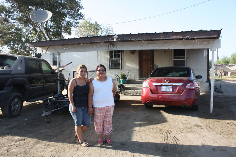 Maria Medina, right, and her 20-year-old daughter Guadalupe outside their Okieville house, where they haven't had running water for 18 months.