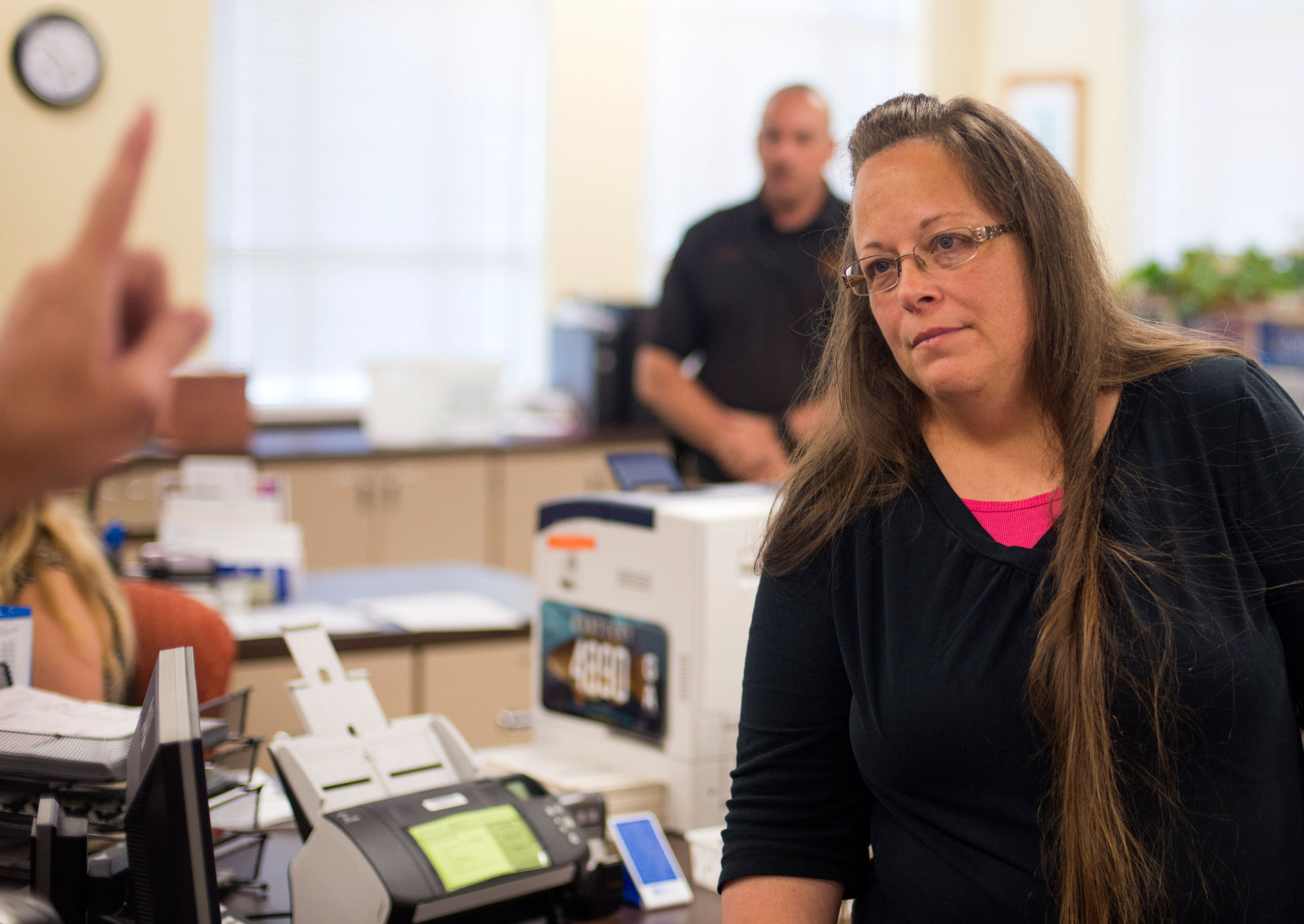 Kim Davis, the Rowan County Clerk of Courts, listens to Robbie Blankenship and Jesse Cruz as they speak with her about getting a marriage license on September 2, 2015 in Morehead, Kentucky.