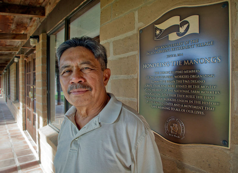 At the Agbayani Village, a retirement home built for the Manongs, Roger Gadiano stands next to a plaque honoring the Manong Filipino workers who started the 1965 grape strike.
