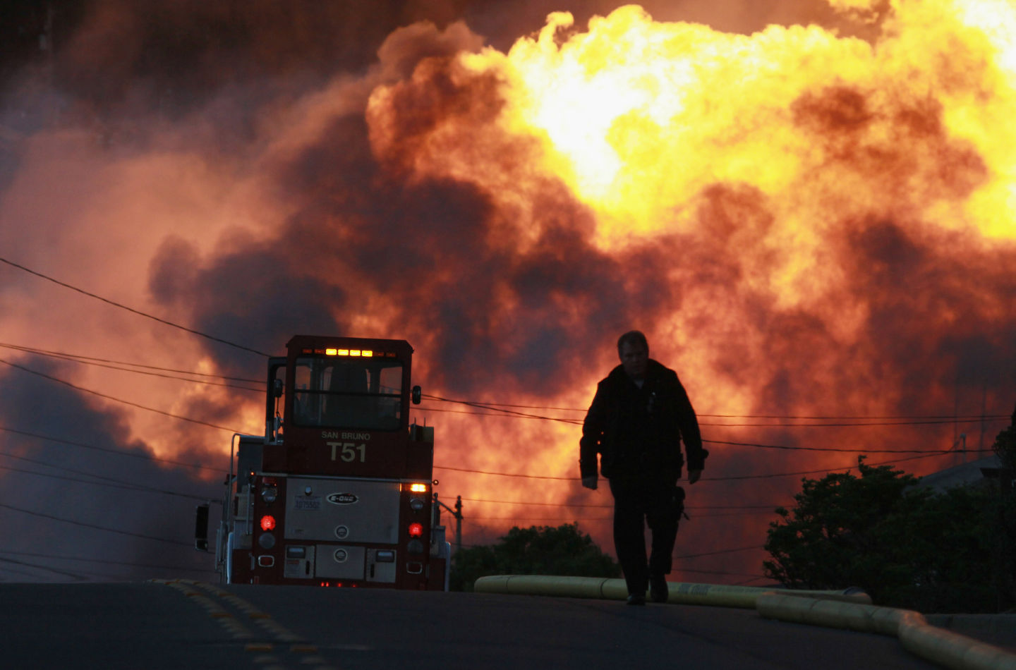 A law enforcement official runs towards a massive fire in the Crestmoor neighborhood of San Bruno on September 9, 2010.