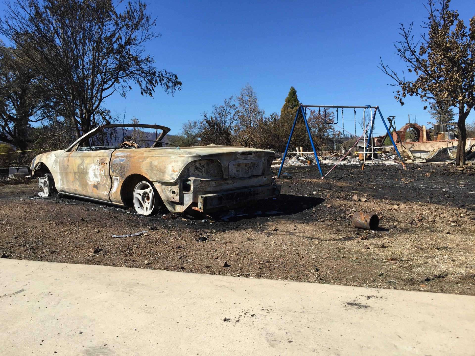 A burned car sits near a swing set in Middletown on Sept. 19, when residents of the community hit hard by the Valley Fire were allowed to return and check their properties.